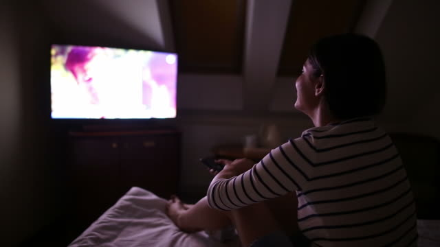 Young woman having fun while watching TV at night. video