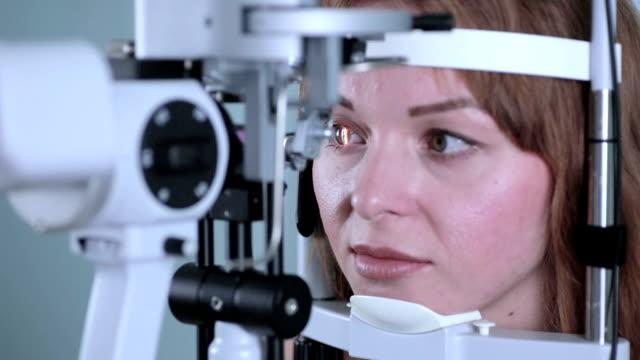 現代の医療機器を用いて彼女の眼を持つ若い女性 - 検眼医点の映像素材/bロール