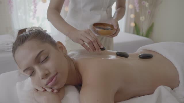 junge frau, die hot-stone-massage im spa, entspannen und aromatherapie - stein baumaterial stock-videos und b-roll-filmmaterial