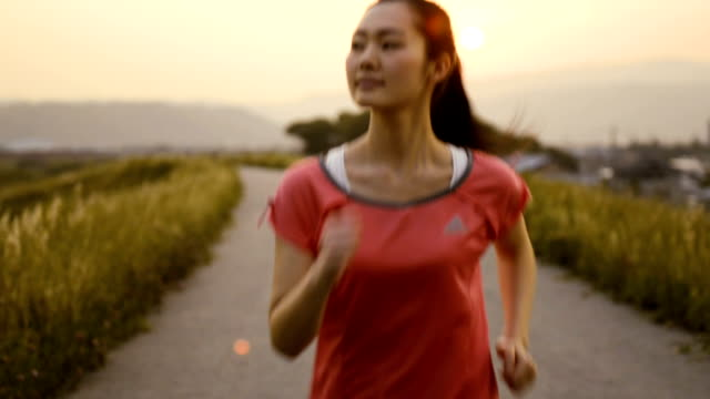 Young woman having jogging at sunset at river bank video