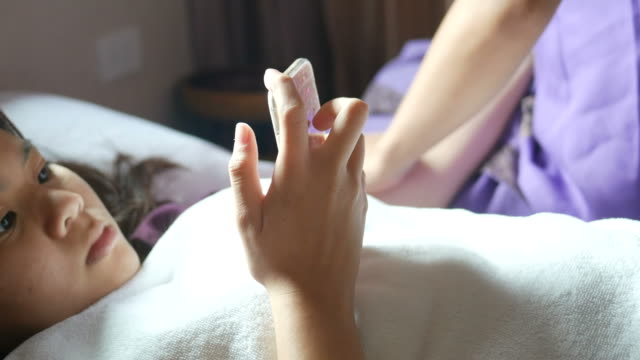 young woman having relaxing  with Thai massage and using phone video