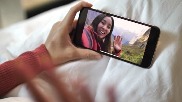 自宅でベッドに横たわって友人にチャットスマートフォンウェブカメラでビデオチャットを持つ若い女性 - テレビ会議 日本人点の映像素材/bロール