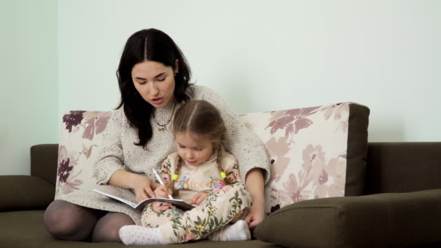 Young woman helps her daughter to make homework video