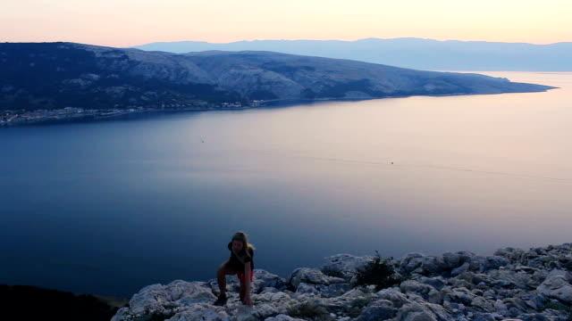 stockvideo's en b-roll-footage met jonge vrouw wandeling op de berg met de zee in sunrise - s