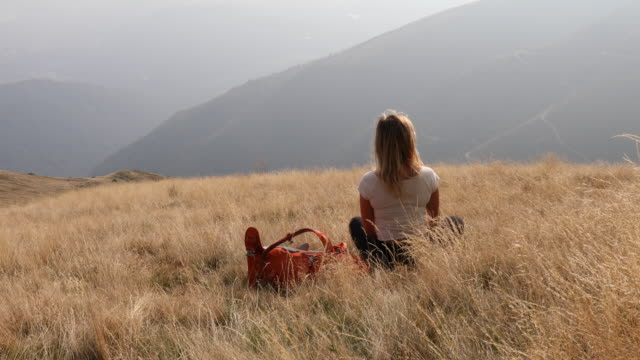 잔디 고산 초원에서 이완 하는 젊은 여자 등산객 - mountain top 스톡 비디오 및 b-롤 화면