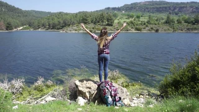 立っている若い女性ハイカーは山湖に近いし、彼の腕を outstretches します。自由の概念。 - フィルタ化点の映像素材/bロール