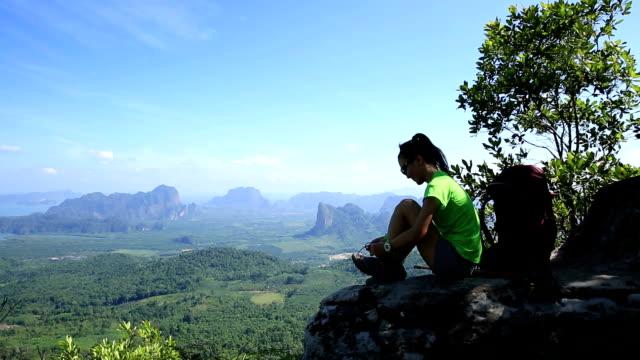young woman hiker tying shoelace on mountain peak video