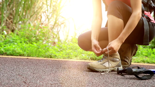 young woman hiker tying shoelaces in the nature video