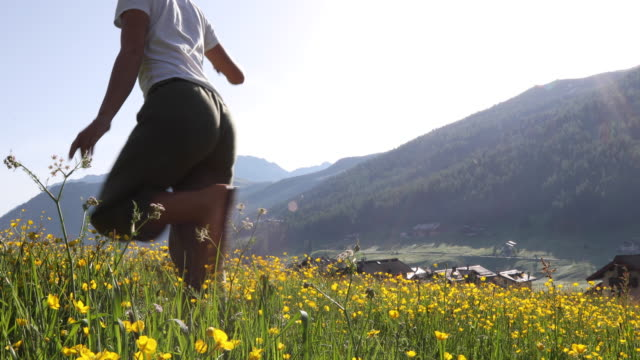 young woman hikes through wildflower meadow at sunrise - livigno video stock e b–roll