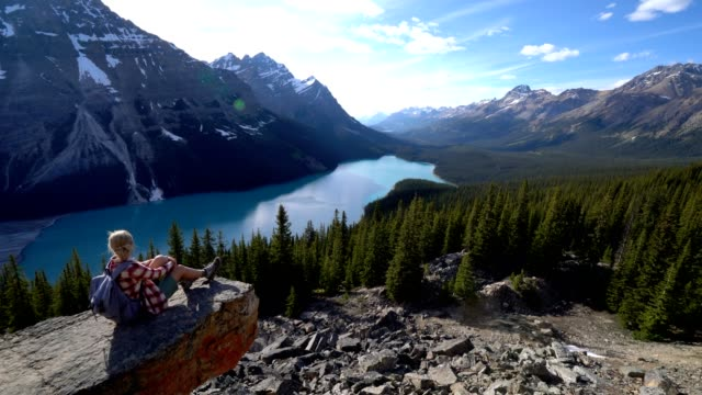 Young woman hiking in the Canadian rockies admires beautiful lake from mountain top video