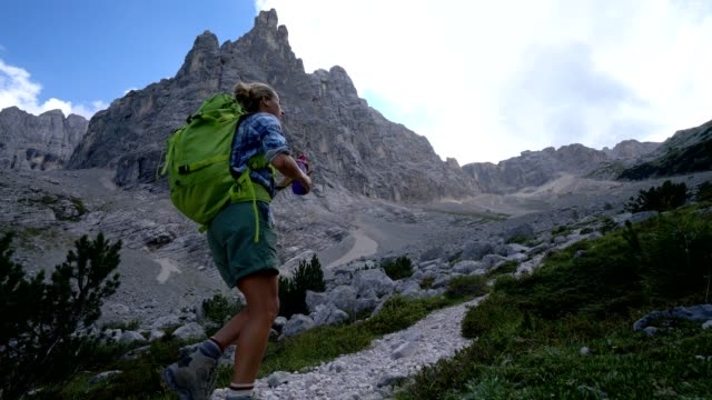 young woman hiking in the dolomites mountains, stops to refresh - ventenne video stock e b–roll