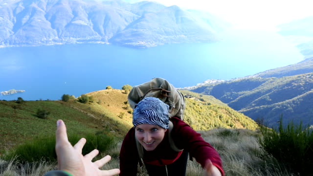 Young woman hiking reaches mountain top, outstretches arms video