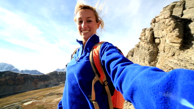 young woman hiking takes selfie on mountain top - young singles stock videos & royalty-free footage