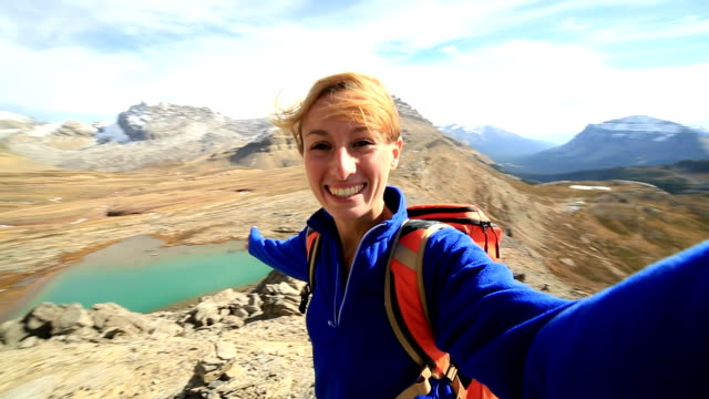 Young woman hiking takes selfie on mountain top video