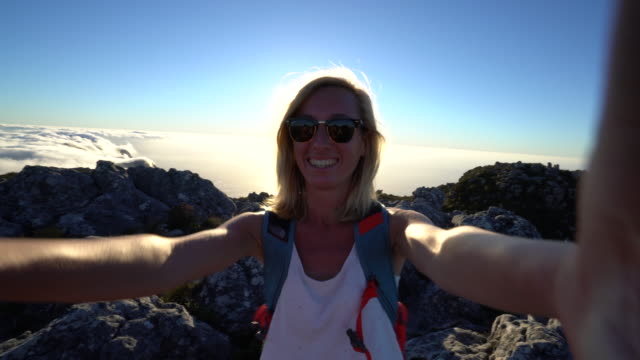 Young woman hiking takes selfie portrait Young woman hiking in Cape Town takes selfie portrait table mountain national park stock videos & royalty-free footage