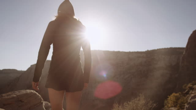 4k uhd: young woman hiking to cliff edge - utah video stock e b–roll