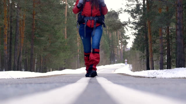 Young woman hiking with a backpack in beautiful winter forest, walking on a asphalt road. video
