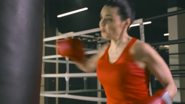 Young woman hitting a boxing bag video