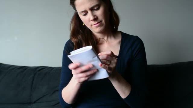 giovane donna in possesso di un blocco note pensare lista di cose da fare - to do list video stock e b–roll