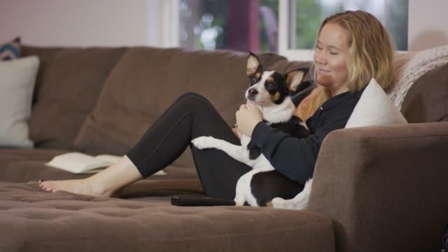 vidéos et rushes de jeune femme tenant un chien sur un canapé - femme seule s'enlacer