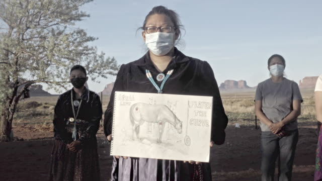 A Young Woman Holding A Drawing, With Her Family In The Background, To Help The Navajo People Understand The Severity Of Covid19
