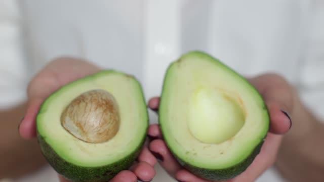 young woman holding a fresh avocado