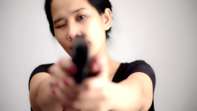 young woman holding a gun young asian woman holding a gun aiming at the camera, with selective focus girl power stock videos & royalty-free footage