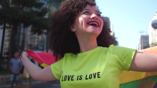 Young woman holding a rainbow flag walking in the street during LGBTQI parade Young woman holding a rainbow flag walking in the street during LGBTQI parade bisexuality stock videos & royalty-free footage