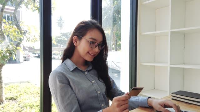 ung kvinna som innehar kredit kort för att göra betalning online shopping med laptop. hem online shopping koncept med kredit kort och laptop - spendera pengar bildbanksvideor och videomaterial från bakom kulisserna