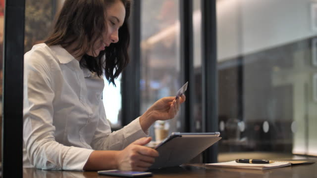 vídeos de stock e filmes b-roll de young woman holding her credit card about to make an online shopping purchase on an ipad digital e-commerce making a decision for online payment concept slow motion - paying with card contactless