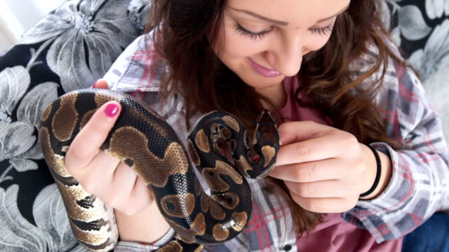 Young woman holding her pet snake