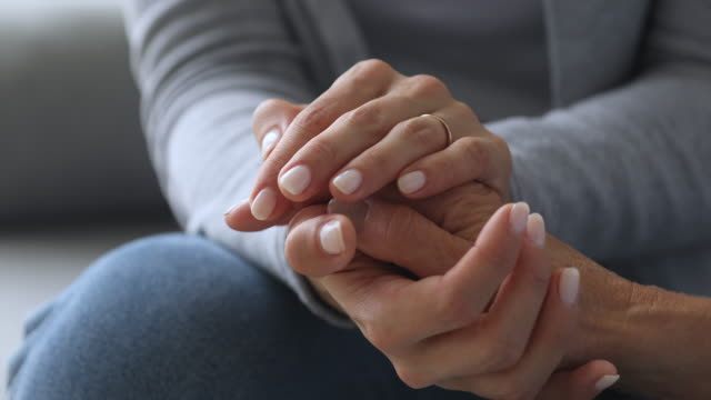 Young woman holding old female hands giving support, close up