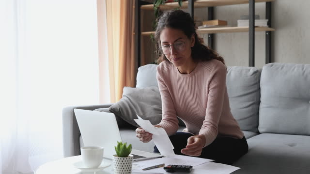 young woman holding paper bills or paychecks calculating money expenses - indennità video stock e b–roll