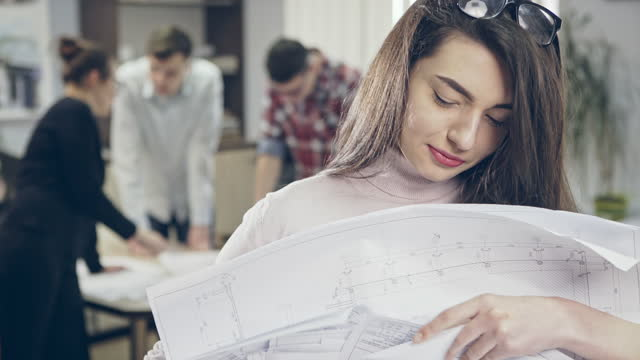 Young woman holding pile of blueprints