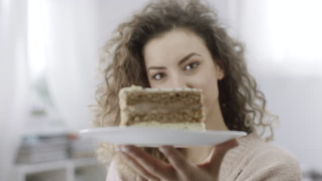 vídeos de stock, filmes e b-roll de placa da terra arrendada da mulher nova com a fatia de bolo nela - tentação
