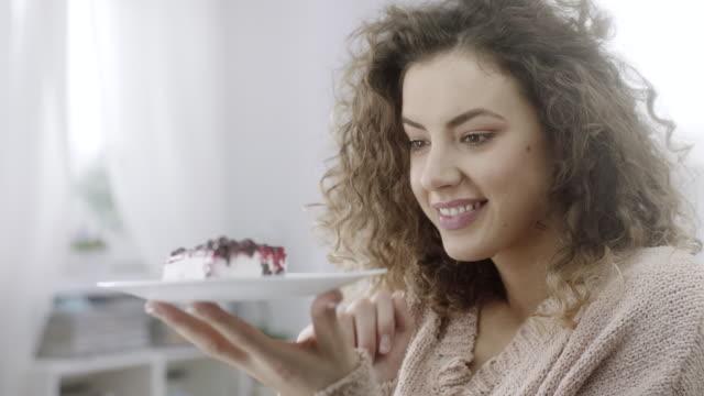 vídeos de stock, filmes e b-roll de placa da terra arrendada da mulher nova com a fatia de cheesecake nela - tentação