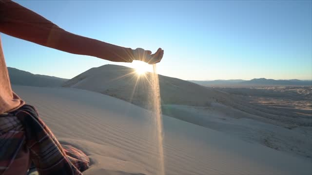 young woman holding sand in hands at sunset; Slow motion video