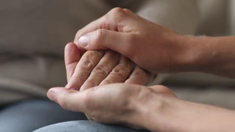 giovane donna che tiene accarezzando la mano femminile del nonno anziano, primo piano - accudire video stock e b–roll