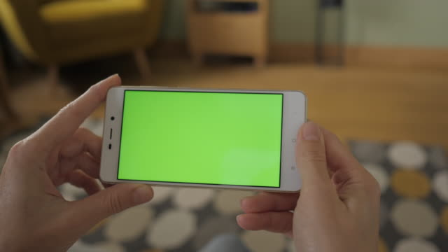 Young Woman Home Sitting on a Couch with Green Screen Smartphone in Horizontal Mode. Girl Using Touch Screen Mobile Phone. Girl Using Smartphone, Browsing Internet, Watching Video Content, Blogs. POV.