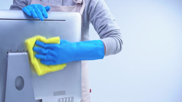 Young woman housekeeper in apron is cleaning, wiping down office computer surface with blue gloves, wet yellow rag.