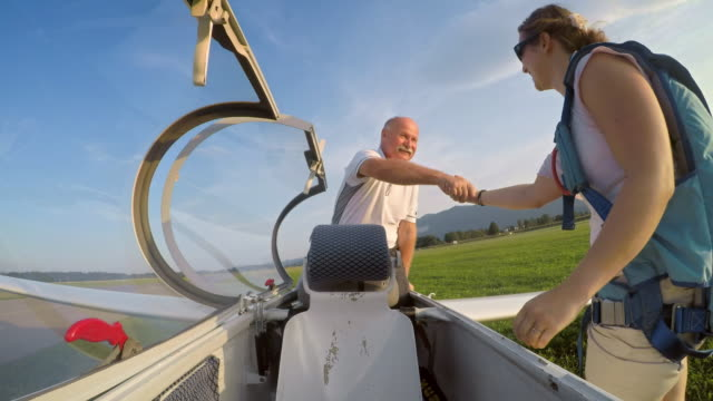LD Young woman hugging the senior pilot of the glider and thanking him for the fun ride