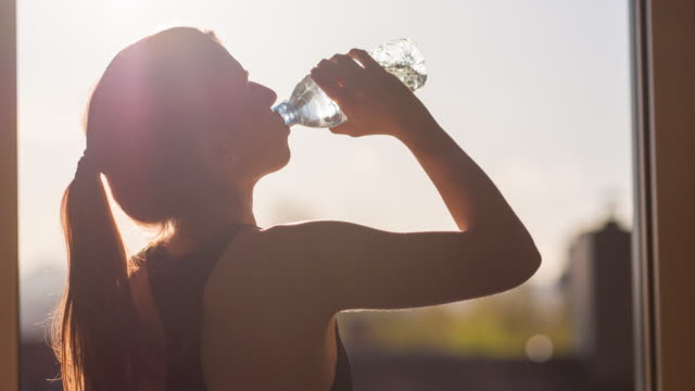 Young woman hydrating after high intensity workout video