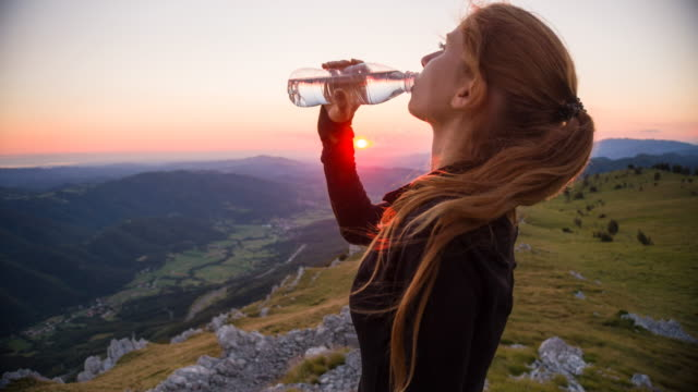 young woman hydrating after reaching the top of a mountain - acqua potabile video stock e b–roll