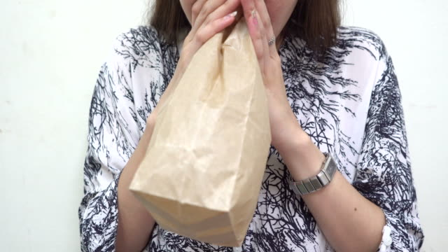 Young Woman Hyperventilating and breathing in paper bag