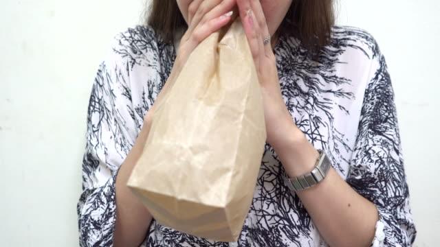 stockvideo's en b-roll-footage met jonge vrouw hyperventilatie en de ademhaling in papieren zak - ongerustheid