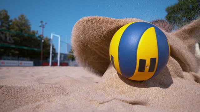 close up: junge frau im bikini taucht in sand bei dem versuch, einen punkt zu erzielen. - trefferversuch stock-videos und b-roll-filmmaterial