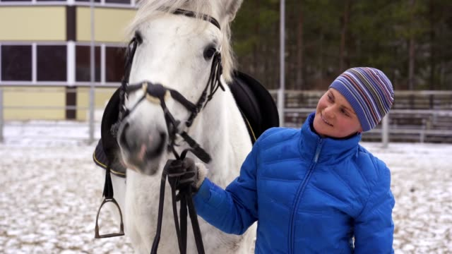 a young woman in a blazer and sports cap strokes a white horse - blazer video stock e b–roll