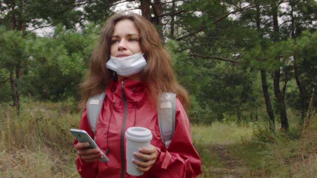 vidéos et rushes de jeune femme dans un masque de coronavirus marchant à travers la forêt avec une tasse de café éco et un smartphone dans ses mains sur une journée d'automne nuageux. - boisson chaude