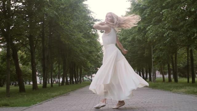 vídeos de stock e filmes b-roll de young woman in a flowing dress dancing on the street. - tule têxtil