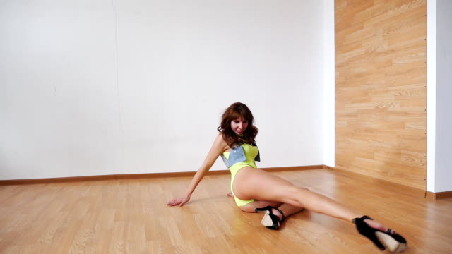 young woman in a green bodysuit, high heels lying on the floor and dancing video
